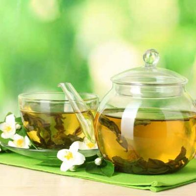 serezniy120703658.jpg - green tea with jasmine in cup and teapot on wooden table on green background
