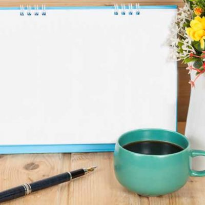 Blank calendar with cup and vase on wood