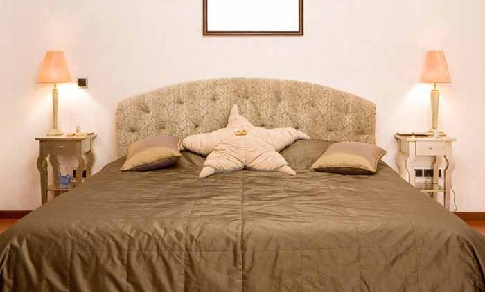 Bedroom in which there is a big bed with a coverlet of olive colour, two little tables with lamps and a pillow in the form of a star